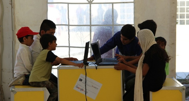 Picture of children using the computers of the Ideas Box at the Eleonas refugee camp in Athens