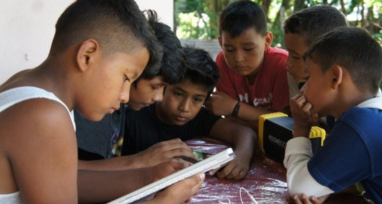 Photo de garçons accédant aux contenus du KoomBook avec une tablette au Nicaragua