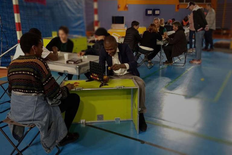 Photo d'herbergés d'urgence en gymnase jouant