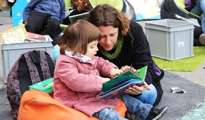 Photo d'une mère et sa fille lui lisant une histoire